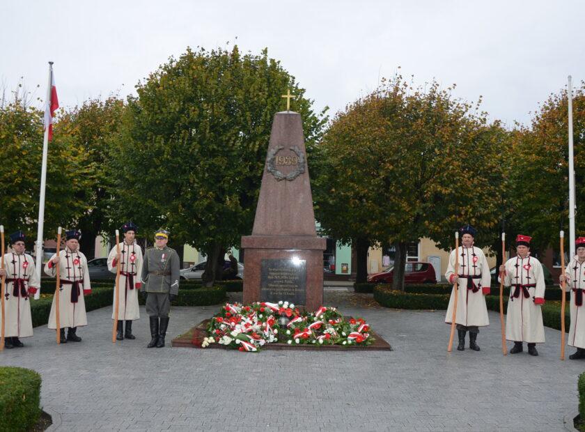 Zdjęcie przedstawia kosynierów przy pomniku na rynku w ksiązu